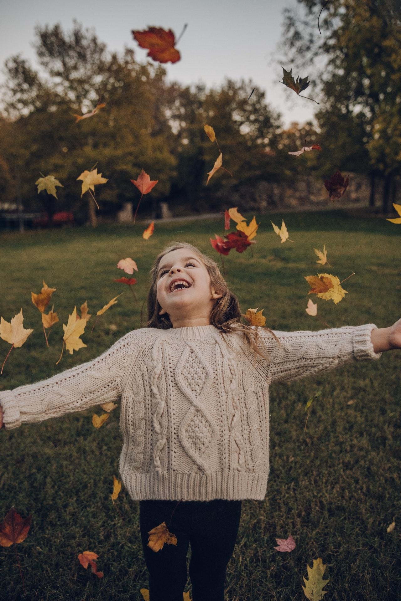 Holčička si hraje v podzimním listí.